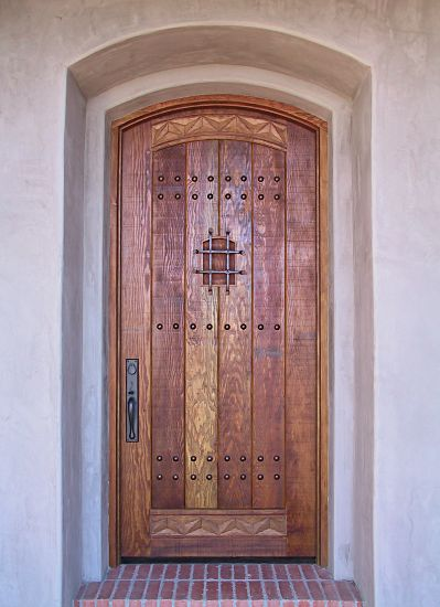 arched rustic door with carving and wrought iron grill